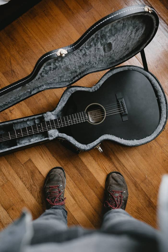 brown acoustic guitar on black guitar stand